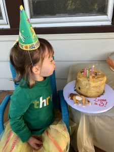 Little girl blowing out candles on cake, with a dead frosting lion lying on the platter.