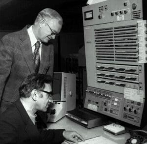Men in front of large 1960s computer console.