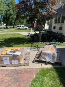 Pallets of boxes in driveway.